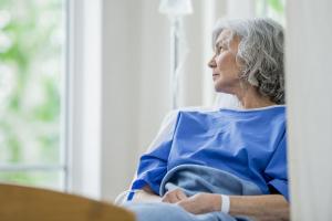 Mujer adulto mayor en hospital mirando por la ventana