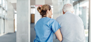 Médico ayudando a adulto mayor a caminar