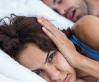 Mujer tapa sus oídos para no escuchar ronquidos de su pareja.