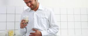 Hombre con mano en su barriga por dolor de acidez