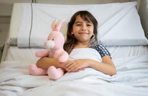 Niña en hospital acostada con su peluche de conejo rosado al lado