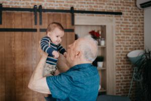 Adulto mayor tomando en brazos a un bebé