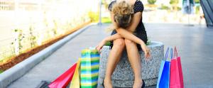 Mujer con bolsas de compras arrepentida de haber comprado