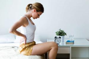 Mujer sentada en una cama con los brazos en la cadera