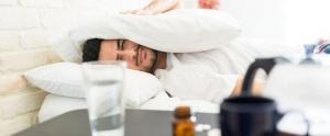 Hombre apretandose la cabeza con una almohada - resaca