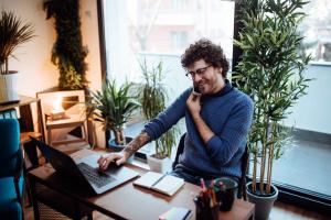Hombre teletrabajando desde casa hablando por teléfono y viendo el computador