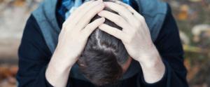 Hombre sujeta su cabeza con ambas manos en señal de malestar - Estrés Postraumático