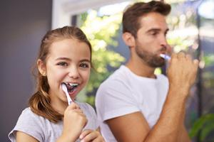 Un hombre y una niña a su lado se lavan los dientes