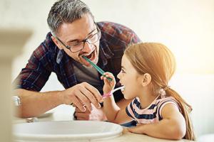 Papá e hija se lavan los dientes