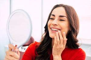 Mujer ve en un espejo cómo quedaron sus dientes