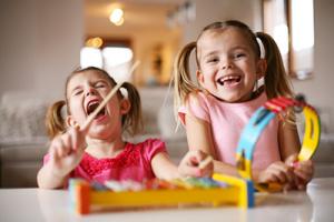 niños hiperactivos - dos niñas practicando música y sonriendo