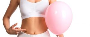 mujer señalando a su estomago sujetando un globo - Balón Intragástrico elipse